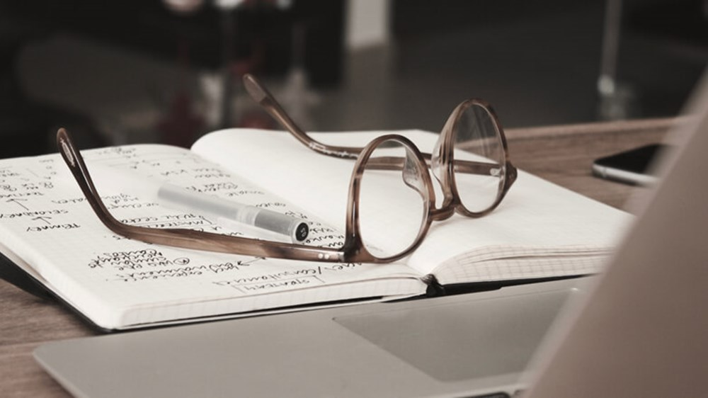 Notepad and glasses on table | Wealthify